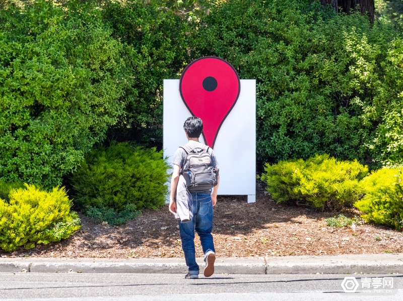 Person walking in front of the Google Maps Icon